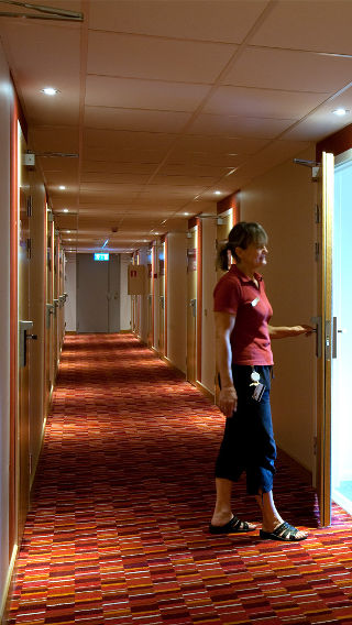 A woman stands in a Spar Hotel corridor, illuminated by Philips hotel lighting