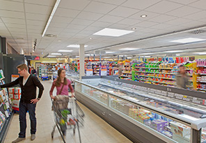 Couple is walking in the aisles of a supermarket illuminates with Philips energy efficient lighting