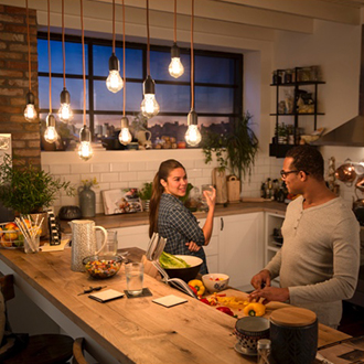 Couple talking underneath Philips vintage LED bulbs hanging from the ceiling creating a cozy warm glow