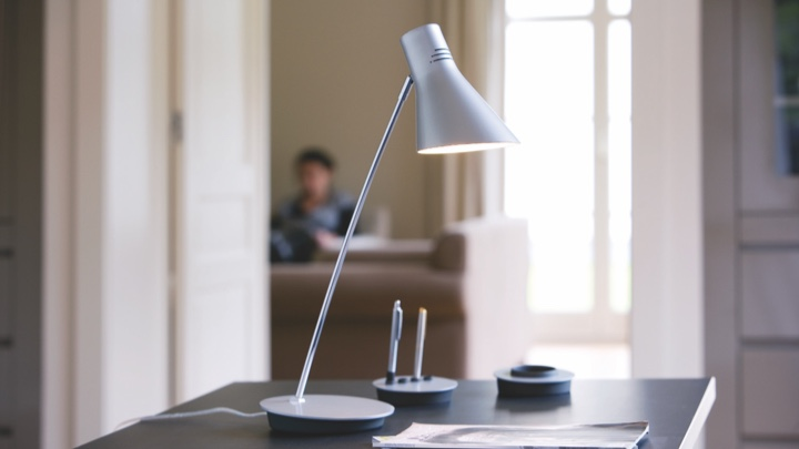 A table lamp on a desk aimed at paper and pen
