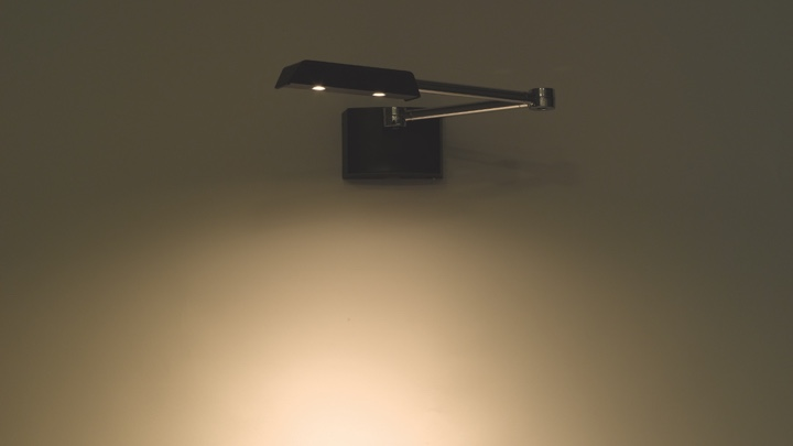 An adjustable lamp fixated at a wall