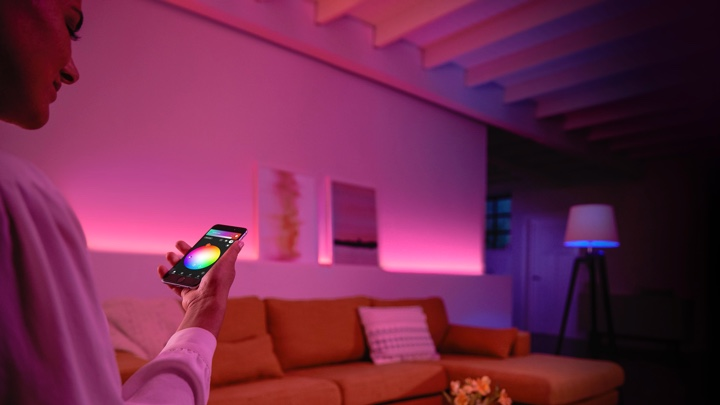 Person controlling colored lights in the living room